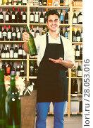 Купить «seller in apron holding bottle of wine», фото № 28053016, снято 20 мая 2019 г. (c) Яков Филимонов / Фотобанк Лори