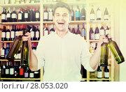 Купить «portrait of man choosing bottle of wine in shop», фото № 28053020, снято 22 октября 2018 г. (c) Яков Филимонов / Фотобанк Лори
