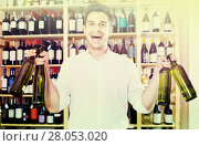 Купить «portrait of man choosing bottle of wine in shop», фото № 28053020, снято 16 августа 2018 г. (c) Яков Филимонов / Фотобанк Лори