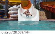 Купить «Grandpa with granddaughter sliding on water slide in water park», видеоролик № 28059144, снято 16 июня 2014 г. (c) Алексей Кузнецов / Фотобанк Лори