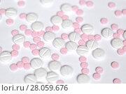 Купить «Рассыпанные таблетки на белом фоне», фото № 28059676, снято 2 января 2018 г. (c) Роман Рожков / Фотобанк Лори