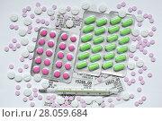 Купить «Таблетки в блистерной упаковке и россыпью на белом фоне», фото № 28059684, снято 2 января 2018 г. (c) Роман Рожков / Фотобанк Лори