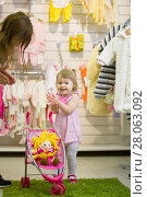 Купить «Little cute blue-eyed blonde girl clapping her hands in the kids' store with the toy baby carriage», фото № 28063092, снято 11 мая 2017 г. (c) Константин Шишкин / Фотобанк Лори