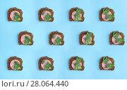 Купить «Коллаж и фон из бутербродов с колбасой на голубом фоне», фото № 28064440, снято 17 февраля 2018 г. (c) V.Ivantsov / Фотобанк Лори
