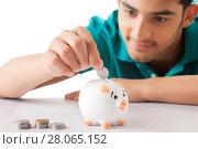 Купить «Young men dropping a coin in the piggy bank», фото № 28065152, снято 25 июня 2014 г. (c) easy Fotostock / Фотобанк Лори