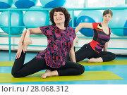 Купить «Women doing yoga exercise in the gym», фото № 28068312, снято 18 февраля 2018 г. (c) Владимир Мельников / Фотобанк Лори