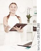 Купить «Smiling woman holding clipboard in company office indoors», фото № 28070280, снято 28 мая 2020 г. (c) Яков Филимонов / Фотобанк Лори