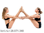Купить «two female athletes doing stretching exercises on white background», фото № 28071340, снято 7 октября 2017 г. (c) Константин Лабунский / Фотобанк Лори