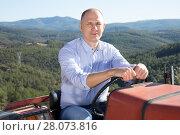 Купить «Male owner of vineyard driving tractor», фото № 28073816, снято 22 января 2018 г. (c) Яков Филимонов / Фотобанк Лори