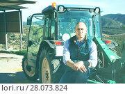 Купить «Confident male owner of vineyard posing near tractor outdoors in», фото № 28073824, снято 22 января 2018 г. (c) Яков Филимонов / Фотобанк Лори