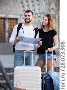 Купить «Couple of smiling tourists with map and baggage», фото № 28073908, снято 25 мая 2017 г. (c) Яков Филимонов / Фотобанк Лори