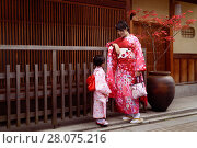 Купить «Mother and her little daughter wearing red traditional Japanese yuakatas, informal kimono on the streets of Gion, Kyoto, Japan.», фото № 28075216, снято 19 ноября 2017 г. (c) age Fotostock / Фотобанк Лори