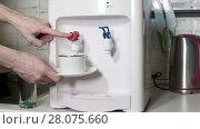 Купить «Человек наливает горячую воду в чашку из кулера на кухне», видеоролик № 28075660, снято 26 февраля 2018 г. (c) Кекяляйнен Андрей / Фотобанк Лори