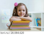 Купить «Happy kid girl with a stack of books at home», фото № 28084620, снято 6 марта 2020 г. (c) Оксана Кузьмина / Фотобанк Лори