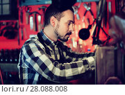 Купить «Male worker working on leather for belt in leather», фото № 28088008, снято 23 июля 2018 г. (c) Яков Филимонов / Фотобанк Лори