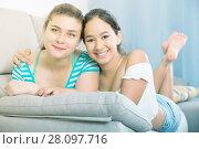 Two cheerful teenagers girls on sofa. Стоковое фото, фотограф Яков Филимонов / Фотобанк Лори