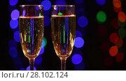 Купить «Two glasses with champagne in front of black background with colorful flashing lights», видеоролик № 28102124, снято 12 февраля 2016 г. (c) Алексей Кузнецов / Фотобанк Лори