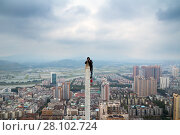 Купить «Roofer shoots from tall spire in residential area in Hong Kong, China», фото № 28102724, снято 2 февраля 2016 г. (c) Losevsky Pavel / Фотобанк Лори
