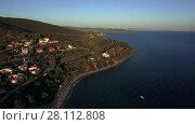 Купить «Coastal town with cottages on the shore and green hills, aerial», видеоролик № 28112808, снято 28 декабря 2017 г. (c) Данил Руденко / Фотобанк Лори
