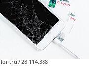 Купить «Смартфон с разбитым дисплеем на нескольких тысячных купюрах», фото № 28114388, снято 3 января 2018 г. (c) Наталья Гармашева / Фотобанк Лори