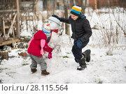 Купить «Children mold Snowman», фото № 28115564, снято 27 февраля 2018 г. (c) Типляшина Евгения / Фотобанк Лори