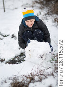 The boy is molded Snowman in the yard in the winter. Стоковое фото, фотограф Типляшина Евгения / Фотобанк Лори