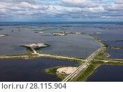 Купить «Oil field on the Samotlor lake, top view», фото № 28115904, снято 21 июня 2017 г. (c) Владимир Мельников / Фотобанк Лори