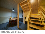 Купить «Interior of wooden house, kitchen with table and chairs, stairs to second floor», фото № 28115972, снято 3 февраля 2017 г. (c) Losevsky Pavel / Фотобанк Лори