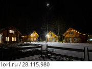Купить «Several illuminated wooden houses on winter evening among trees», фото № 28115980, снято 3 февраля 2017 г. (c) Losevsky Pavel / Фотобанк Лори