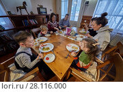 Купить «Three adults and four children eat sitting at wooden table in room», фото № 28116000, снято 4 февраля 2017 г. (c) Losevsky Pavel / Фотобанк Лори