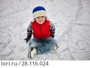 Купить «Little smiling boy on skates sits on ice surface of rink on winter day», фото № 28116024, снято 4 февраля 2017 г. (c) Losevsky Pavel / Фотобанк Лори
