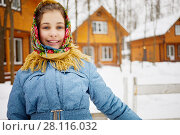 Купить «Smiling teenage girl in folk style shawl stands near fencing against wooden houses on winter day», фото № 28116032, снято 4 февраля 2017 г. (c) Losevsky Pavel / Фотобанк Лори