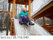 Купить «Two laughing teenage girls ride on snow tube down wooden slide covered with snow on winter day», фото № 28116040, снято 4 февраля 2017 г. (c) Losevsky Pavel / Фотобанк Лори