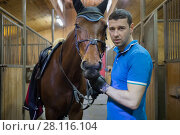 Купить «Handsome man in blue stands with brown horse in harness in stable, focus on horse», фото № 28116104, снято 17 февраля 2017 г. (c) Losevsky Pavel / Фотобанк Лори