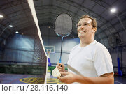 Купить «Smiling man in glasses with badminton racket and shuttlecock near net at sports ground», фото № 28116140, снято 29 октября 2016 г. (c) Losevsky Pavel / Фотобанк Лори