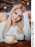 Купить «Young smiling blonde woman sits in cafeteria at table with cup of coffee», фото № 28116244, снято 1 ноября 2016 г. (c) Losevsky Pavel / Фотобанк Лори