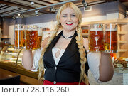 Купить «Smiling blonde woman stands holding several glass mugs with beer in both hands», фото № 28116260, снято 1 ноября 2016 г. (c) Losevsky Pavel / Фотобанк Лори