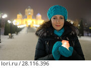 Купить «Woman smiles and holds burning candle in glass pot, Cathedral of Gregory Enlightener with illumination out of fcous, Yerevan, Armenia», фото № 28116396, снято 5 января 2017 г. (c) Losevsky Pavel / Фотобанк Лори
