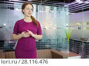 Купить «Pretty woman in dress poses in modern office with sofa and glass walls», фото № 28116476, снято 20 ноября 2016 г. (c) Losevsky Pavel / Фотобанк Лори
