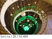 Купить «Empty spiral staircase with green illumination and hanging balls in hotel», фото № 28116480, снято 7 января 2017 г. (c) Losevsky Pavel / Фотобанк Лори