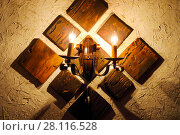 Купить «Wooden retro wall bracket lamp is on wall indoor, warm yellow light», фото № 28116528, снято 7 января 2017 г. (c) Losevsky Pavel / Фотобанк Лори