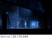 Купить «MOSCOW - JAN 25, 2017: Prisoners behind fence with barbed wire on stage at Passenger performance in Moscow Theater New Opera, Text translation - My Fair March, My tender March», фото № 28116644, снято 25 января 2017 г. (c) Losevsky Pavel / Фотобанк Лори