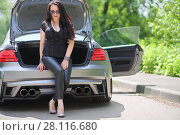 Купить «MOSCOW - JUN 19, 2016: Woman (with model release) with long black hair sitting on the open trunk of a sports car in front of green foliage», фото № 28116680, снято 19 июня 2016 г. (c) Losevsky Pavel / Фотобанк Лори