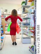 Купить «Woman in red with two bags poses in supermarket Goods for Home, back view», фото № 28116688, снято 14 октября 2016 г. (c) Losevsky Pavel / Фотобанк Лори