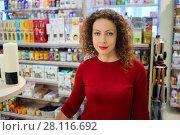 Купить «Smiling woman in red dress poses in supermarket Goods for Home», фото № 28116692, снято 14 октября 2016 г. (c) Losevsky Pavel / Фотобанк Лори