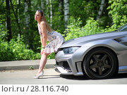 Купить «Young woman with long hair in sundress sitting on the hood of a silver sports car in front of green foliage», фото № 28116740, снято 19 июня 2016 г. (c) Losevsky Pavel / Фотобанк Лори