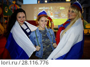 Купить «Three women covered with flags of Russia pose against screen with soccer game outdoor at playground», фото № 28116776, снято 20 июня 2016 г. (c) Losevsky Pavel / Фотобанк Лори