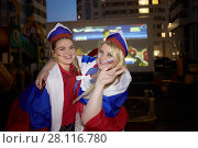 Купить «Two smiling women covered with flags of Russia pose against screen with soccer game outdoor at playground», фото № 28116780, снято 20 июня 2016 г. (c) Losevsky Pavel / Фотобанк Лори