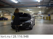 Купить «MOSCOW, RUSSIA - NOV 11, 2015: Young woman (with model release) shuts down hood of the Tesla S car. The Tesla Model S produced by Tesla Motors, and introduced in June 2012.», фото № 28116948, снято 11 ноября 2015 г. (c) Losevsky Pavel / Фотобанк Лори