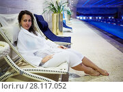 Купить «MOSCOW, RUSSIA - NOV 14, 2015: Young woman in bathing gown sits on lounge at poolside in recreational area in Radisson Royal Ukraine hotel, one of seven Stalin skyscrapers», фото № 28117052, снято 14 ноября 2015 г. (c) Losevsky Pavel / Фотобанк Лори